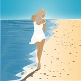 Girl in a dress walking on the beach Royalty Free Stock Photo