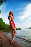 Girl in dress walking on the sea coast in the trees along the sa Royalty Free Stock Image