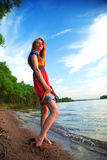 Girl in dress walking on the sea coast in the trees along the sa Royalty Free Stock Images