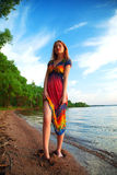 Girl in dress walking on the sea coast in the trees along the sa Stock Photos