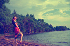 Girl in dress walking on the sea coast in the trees along the sa Royalty Free Stock Photos