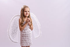 Girl dressed as an angel with wings folded hands Royalty Free Stock Photos