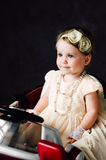 girl dressed as bride playing with toy car Royalty Free Stock Image