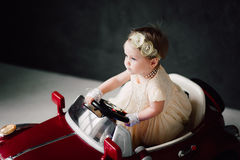 Girl dressed as bride playing with toy car Stock Photo