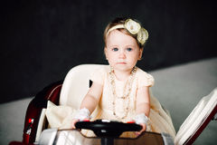 Girl dressed as bride playing with toy car Stock Photography