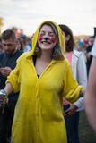 Girl dressed as a clown in yellow clothes partying Stock Photography