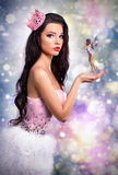 Girl dressed as a princess fairy holds in his hands. fantastic brunette doll on a colorful background,. Close elf flies Royalty Free Stock Photography