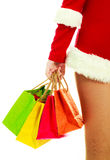 Girl dressed as Santa. Slim girl dressed as Santa with Christmas presents against white background Stock Photo