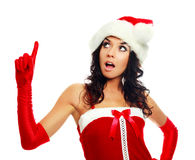 Girl dressed as Santa. Studio portrait of a pretty brunette girl dressed as Santa pointing up Royalty Free Stock Images