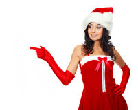 Girl dressed as Santa. Studio portrait of a pretty brunette girl dressed as Santa pointing to the side Stock Photography