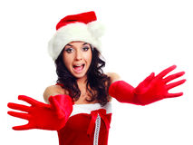 Girl dressed as Santa. Beautiful excited brunette girl dressed as Santa stretching her hands to us Royalty Free Stock Photography