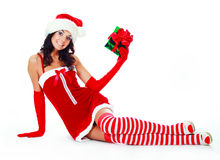 Girl dressed as Santa. Pretty brunette girl dressed as Santa with a Christmas present Royalty Free Stock Photo