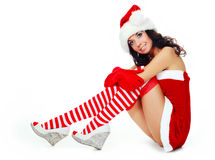 Girl dressed as Santa. Beautiful dreamy brunette girl dressed as Santa sitting on the floor Royalty Free Stock Image