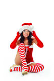 Girl dressed as Santa. Beautiful brunette girl dressed as Santa against white background Royalty Free Stock Photography
