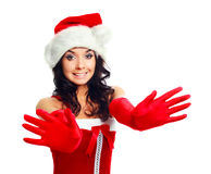 Girl dressed as Santa. Beautiful brunette girl dressed as Santa stretching her hands to us Royalty Free Stock Photography