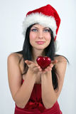 Girl dressed as Santa. Holding a heart Royalty Free Stock Image