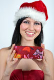 Girl dressed as Santa. Holding a wrapped present Stock Photo