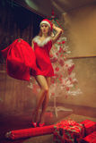Girl dressed as Santa with a bag of gifts and long sexy legs nea Stock Image