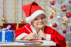 Girl dressed as Santa Claus with glasses and drawing card for Christmas Stock Images