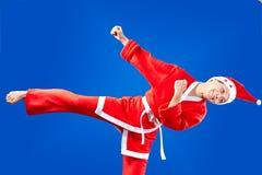 Girl dressed as Santa Claus hits a kick leg Stock Photography