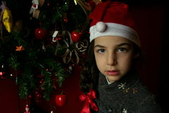 Girl dressed as Santa Claus. Little girl with hat of Santa Claus, Christmas tree near her Stock Photo