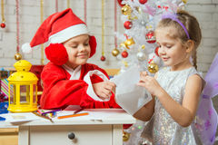 Girl dressed as Santa Claus puts a congratulatory letter in the envelope that holds the girl fairy Stock Images