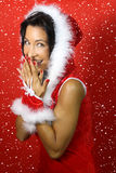 Girl dressed as santa claus smilesd. Girl dressed as santa claus smiles on a red background stock images