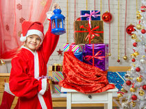 Girl dressed as Santa Claus stands with a candlestick in his hand a bag with Christmas gifts Stock Images