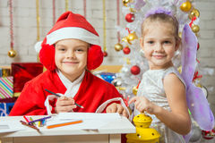 Girl dressed as Santa Claus writing a letter, standing next to a fairy with a flashlight in his hand Royalty Free Stock Image