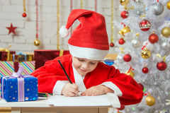 Girl dressed as Santa Claus writing a list of desired gifts for Christmas Royalty Free Stock Photo