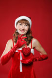 Girl dressed as Santa and heart in her hands. Royalty Free Stock Photo