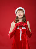 Girl dressed as Santa and heart in her hands. Royalty Free Stock Image