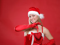 Girl dressed as Santa and heart in her hands. Royalty Free Stock Photos