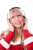 Girl dressed as Santa listening to the music Stock Photos