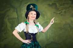 A girl dressed as St. Patrick points with her finger against a g. Reen background. St. Patrick`s Day Stock Images