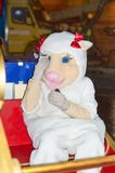 A girl dressed as a white pig sits on a bench for photographs of passers-by. stock photography
