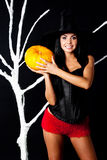 Girl dressed as a witch holding a pumpkin. Slender girl dressed as a witch holding a pumpkin at the tree at Royalty Free Stock Image