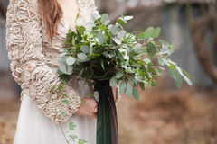 Girl dressed in beige colours. Is holding green wedding bouquet of eucalyptus, ivy, fern, aspidistra, ruskus, date fruit, pink, ranunkulyus with green and brown Royalty Free Stock Images