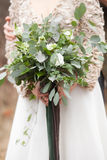 Girl dressed in beigecolours. Girl dressed in beige colours is holding green wedding bouquet of eucalyptus, ivy, fern, aspidistra, ruskus, date fruit, pink Stock Photo