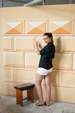 Girl dressed in black and white decorating a wall Royalty Free Stock Photo