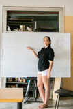 Girl dressed in black and white in front of a white board Royalty Free Stock Image