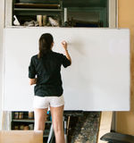 Girl dressed in black and white in front of a white board Stock Image