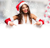 Girl dressed for Christmas showing a blank board Royalty Free Stock Photography