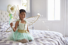 Girl Dressed In Fairy Costume Sitting On Bed At Home Royalty Free Stock Image