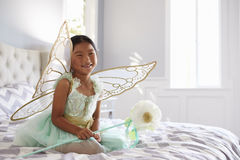Girl Dressed In Fairy Costume Sitting On Bed At Home Stock Photo