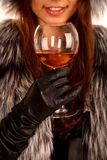 Girl dressed in a fur coat keeps a glass and smile. The girl dressed in a fur coat keeps in a hand a glass with an alcoholic drink and smiling Stock Photo
