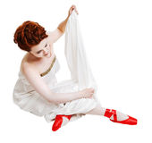 Girl dressed in greek costume sitting on white Stock Images