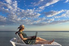 The girl is dressed in a hat and dress, lying on a chaise longue and holding a computer, a freelancer on a blue sea and sky backgr stock photos