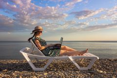 The girl is dressed in a hat and dress, lying on a chaise longue and holding a computer, a freelancer on a blue sea and sky backgr royalty free stock photo