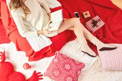 Girl dressed knitted dress and knitted socks lies and reads a book on red-white blankets and pillows with, red cup of stock photo